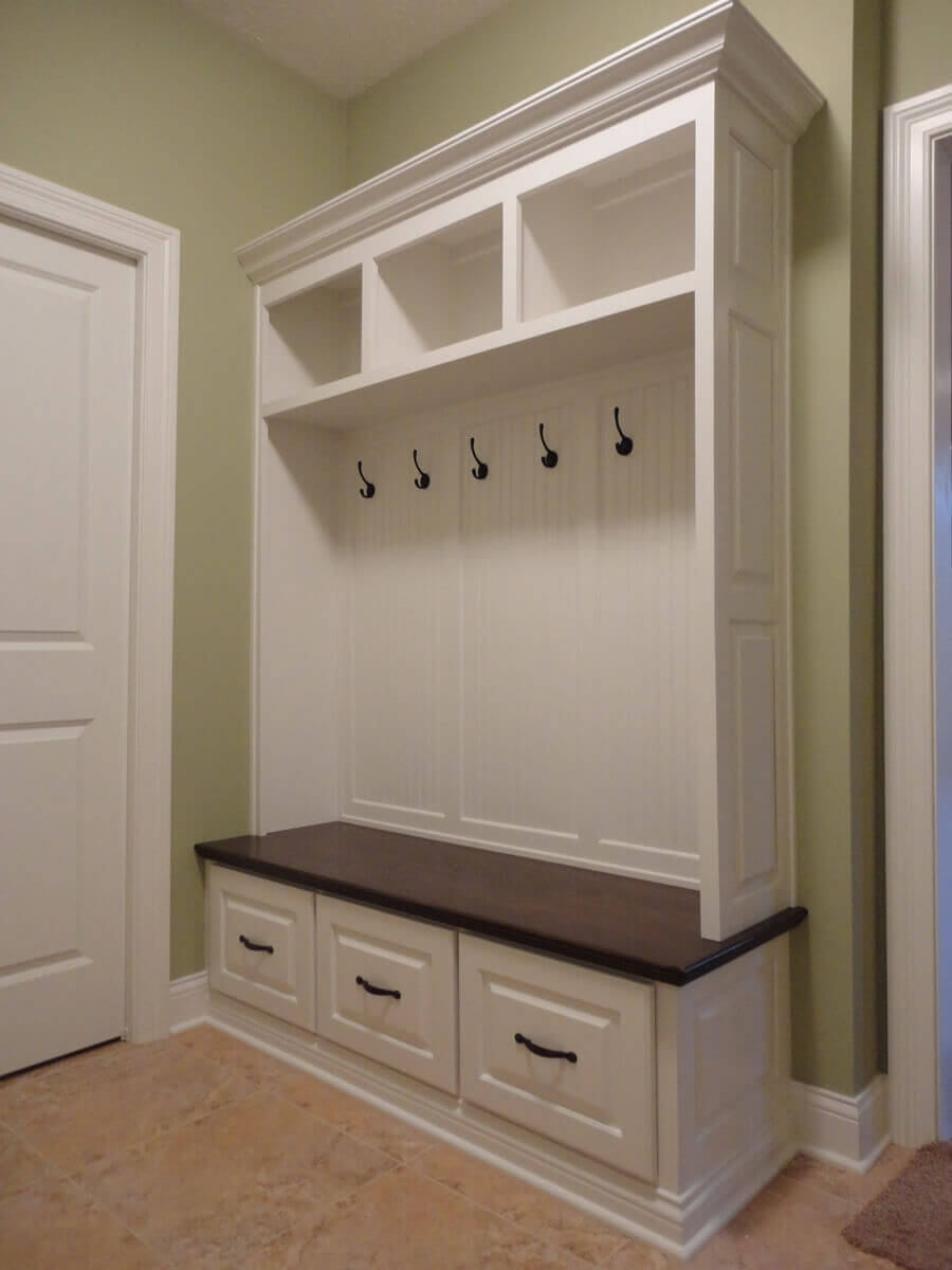 Entryway with white open storage lockers and shelf with hooks
