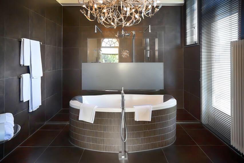 Brown master bath large chandelier