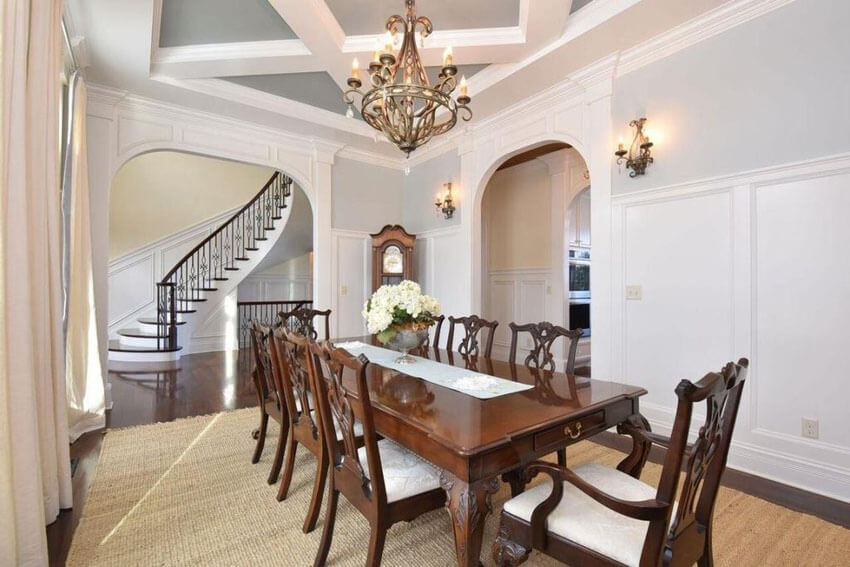 Formal dining room with high white wainscoting and upper gray paint design