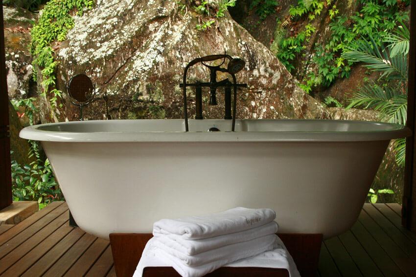 gorgeous outside bathtub next to rock wall