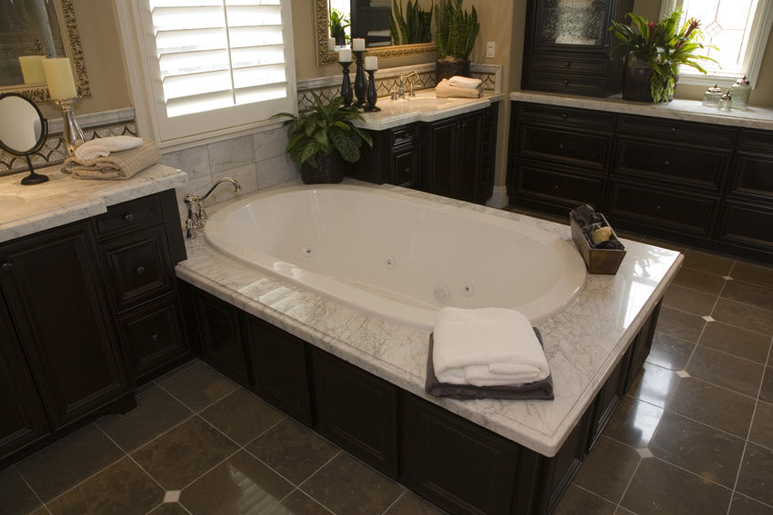 large jet tub in bathroom suite with dark cabinets