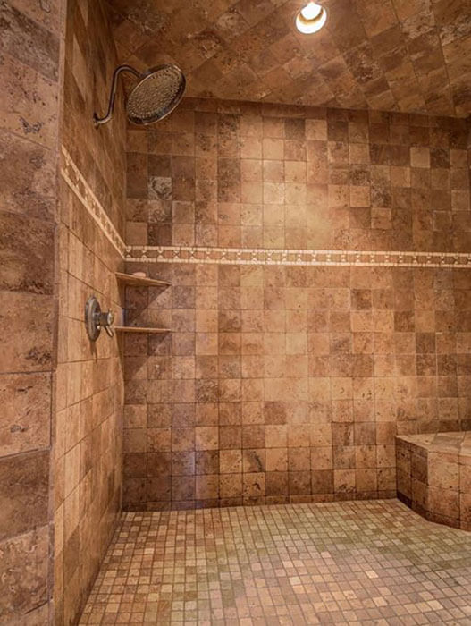 large travertine shower with corner bench