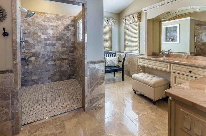 luxury shower with travertine tile in cream color vanity bathroom