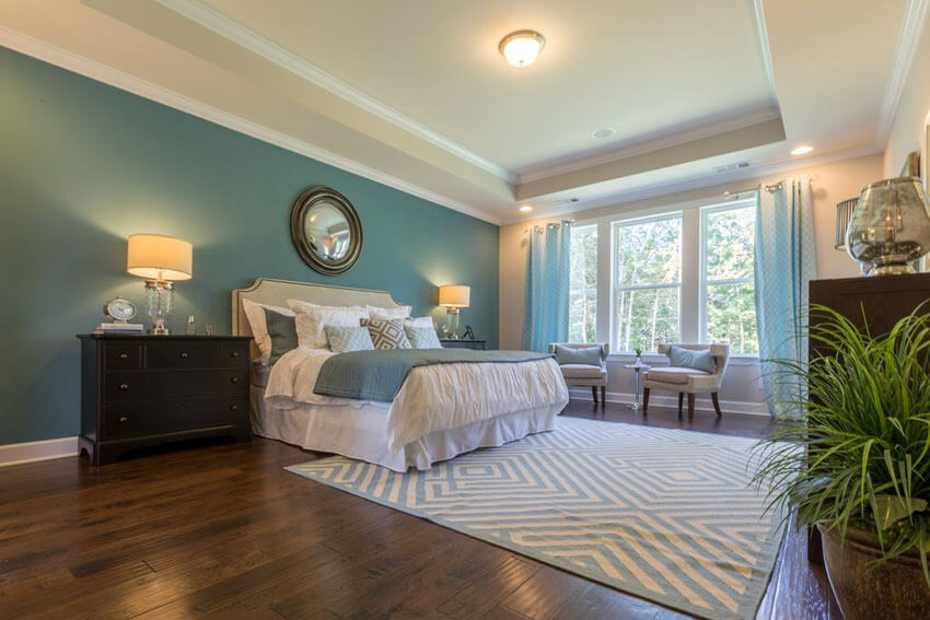 Luxury Teal Master Bedroom with Tray Ceiling Wood Floors and Area Rug