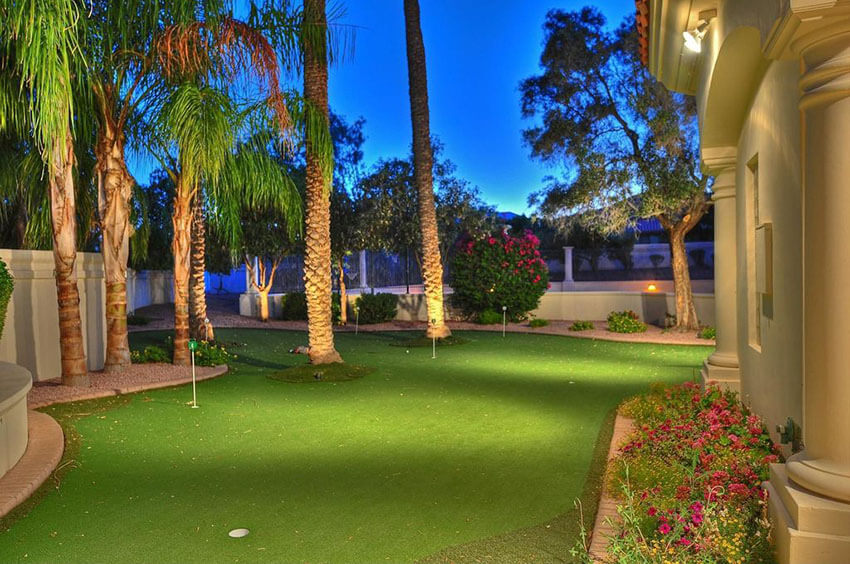 backyard golf green with tropical plants at luxury home