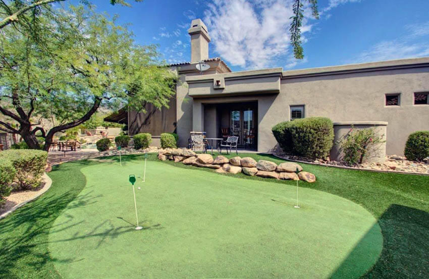large backyard putting green with rock landscaping