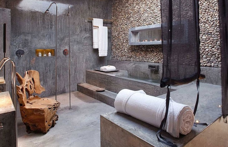 Original design of bathroom with rolled stone wall and cement wall