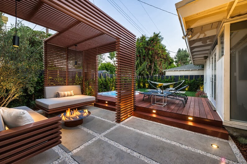 Terrace with the wooden slats floor tiles and table with fireplace