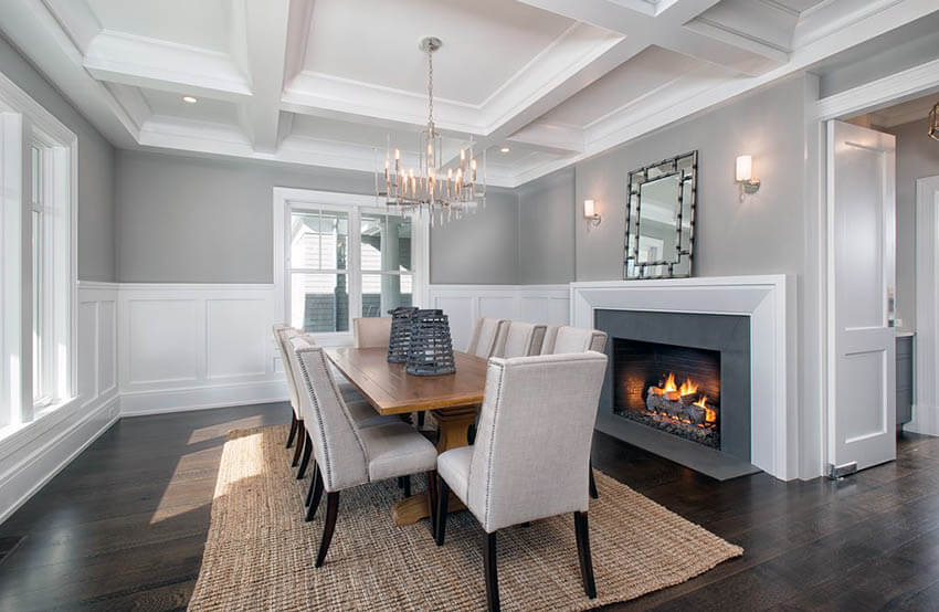 dining room with silver chandelier white wainscoting dark wood floors and gray painted walls