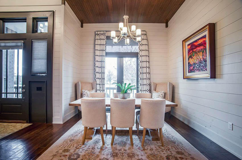 dining room with white shiplap walls and dark wood floors with area rug