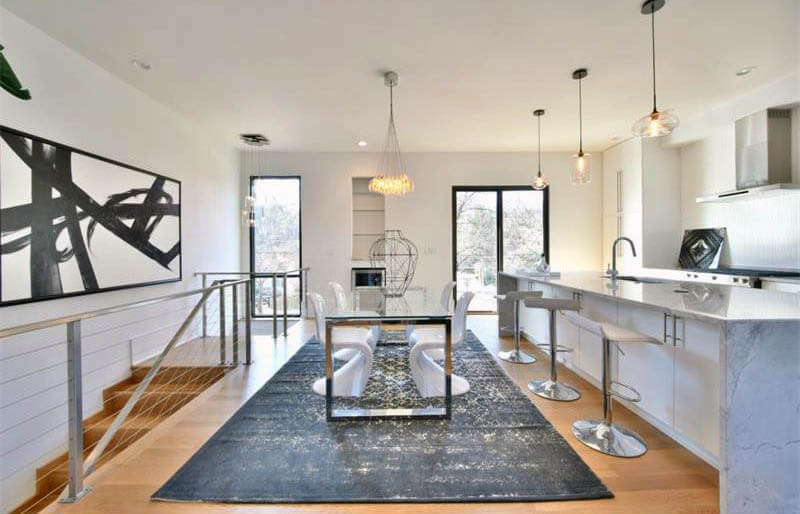 modern dining room and kitchen with cluster pendant lights above table