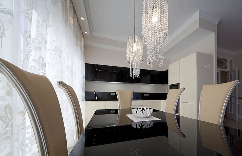 modern dining room with two small hanging crystal chandeliers and black and white color palette