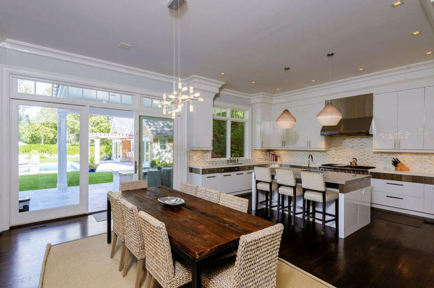 open plan contemporary kitchen with island gray qaurtz countertops and rustic wood dining table