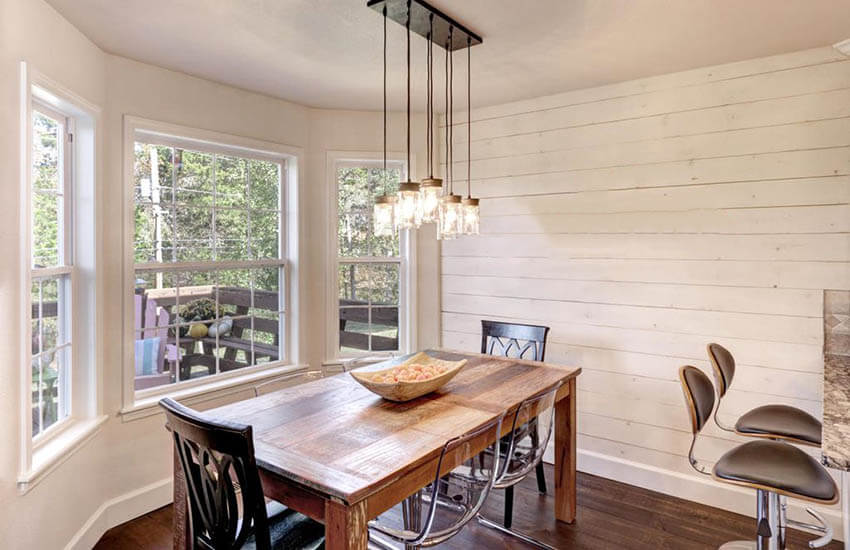 rustic dining room with painted shiplap wall and wood table