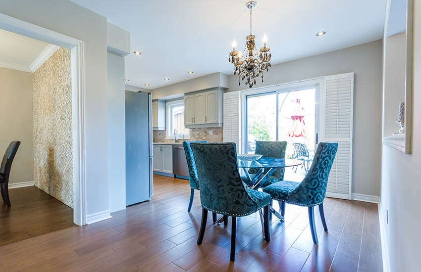 small dining room off kitchen with glam candle style chandelier and recessed lights