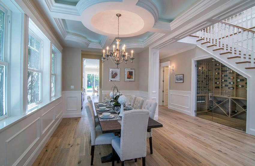 traditional dining room with chandelier beige paint and white wainscoting