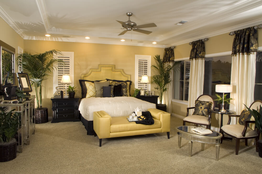 Best feng shui colors for master bedroom - White ceiling with ceiling fan. At night beautifully lighted modern bedroom with two white and black chairs and drapes, yellow loveseat and walls and plenty of plants.