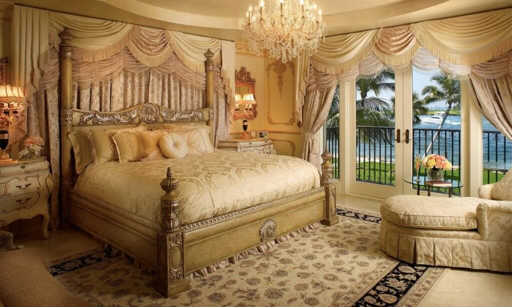 Best idea coastal luxury master bedroom modern furniture. Golden chandelier , white double doors overlooking the ocean, light king size bed with light carpet and luxurious resting chair with reading table.