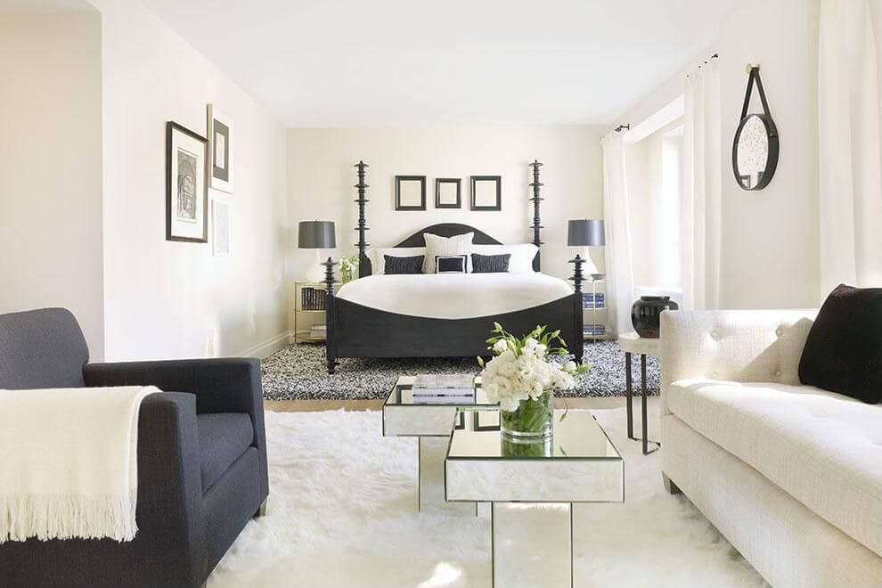 Decorating master bedroom with white walls and black chair & bed with white sheets and pillows. stunning white walls, carpet and 2 seat sofa. Plenty of sunlight can enter through big white glass transparent windows. The mini-tables are made out of mirrors.