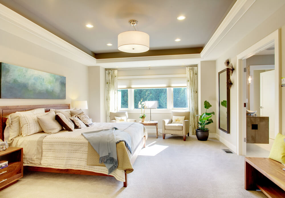 Decorating master bedroom with white walls, dark ceiling and small chandelier with four ceiling light spots. Brown furniture like the bed frame, and brown night stand in contrast with the white flooring carpet and bed sheets.