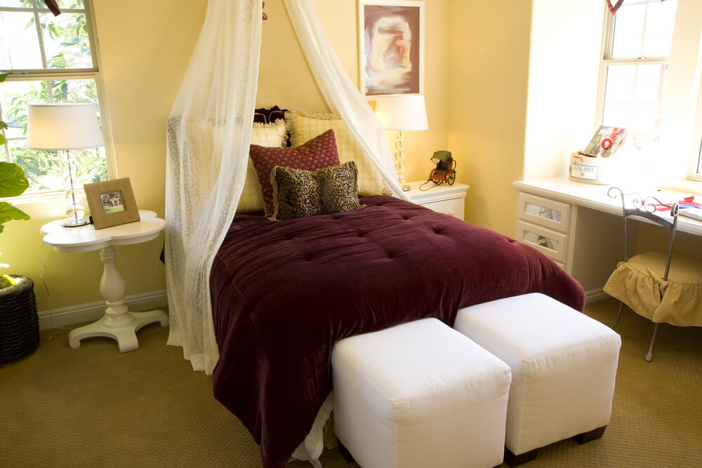 Ex large rooms - luxury master bedrooms - a queen size bed with purple bed cover and pillows. In contrast with pale yellow walls, white table and white chair. Natural light comes through the big clear windows. Two chairs are in front of the bed to add dimension.