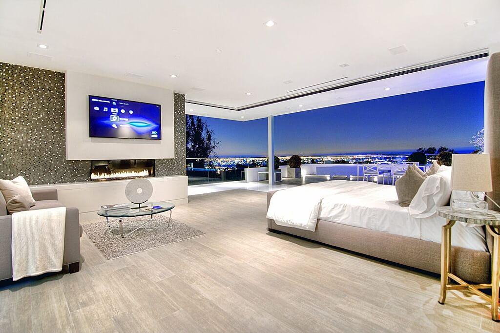 How to decorate your master bedroom wall pictures - retractile window glass wall with a panoramic view of the bay. Modern architecture with grey furniture and gray sofa. Modern TV and gray hardwood flooring design and ideas.