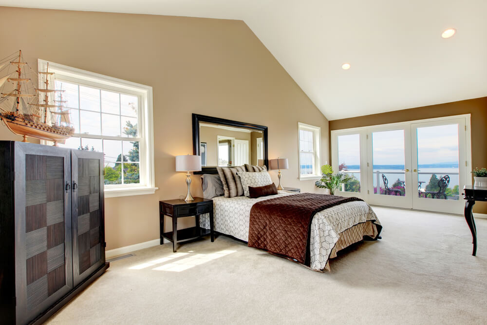 Modern interior design master bedroom paint colors beige & white ceiling. This attic luxury modern master bedroom has a great outside view of the bay, simple dark furniture and mirror frame in contrast with everything else.