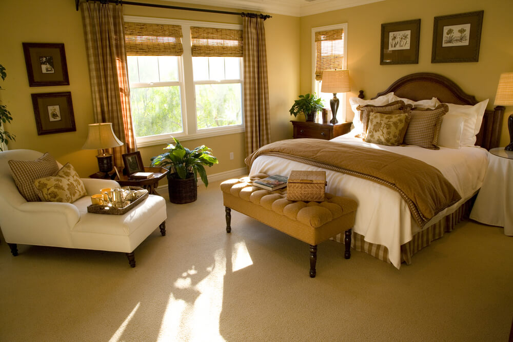 Luxury bedroom comforter sets queen size. Beautiful master bedroom with plenty of sun light, brown drapes and beige rug and plant. Comfortable white chair for reading and relaxing as well as serving coffee. walls with photos ideas and designs. Two bed lamps that add style and luxury.