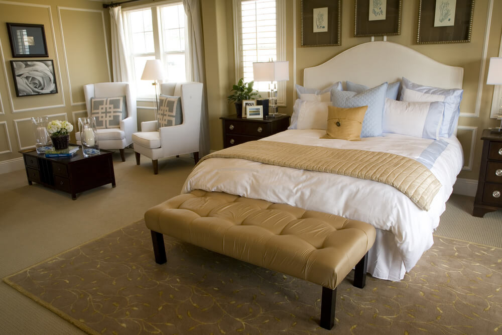 Luxury bedroom decorating ideas and pictures - Large white bed with two separate white chairs perfect for reading or enjoying coffee. Small dark color coffee table and night stands. Beige carpet and walls with dark rug over the light color carpet.