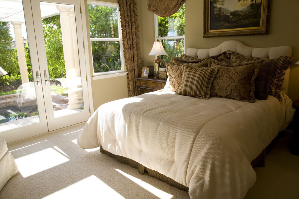 Luxury bedroom furniture pictures - overlooking the garden from the comfort of your bedroom, plenty of sunlight. Light color carpet and walls, colorful pillows and beautiful room painting. Slim drapes that hide small windows. The room has a door frame with open double door.