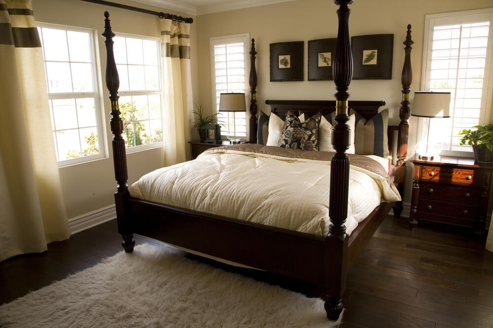 Luxury king size luxury master bedroom comforter sets - dark wood frame bed with dark floor and white carpet. White walls and white drapes in contrast with dark wooded night stands and frame picture ideas and designs.