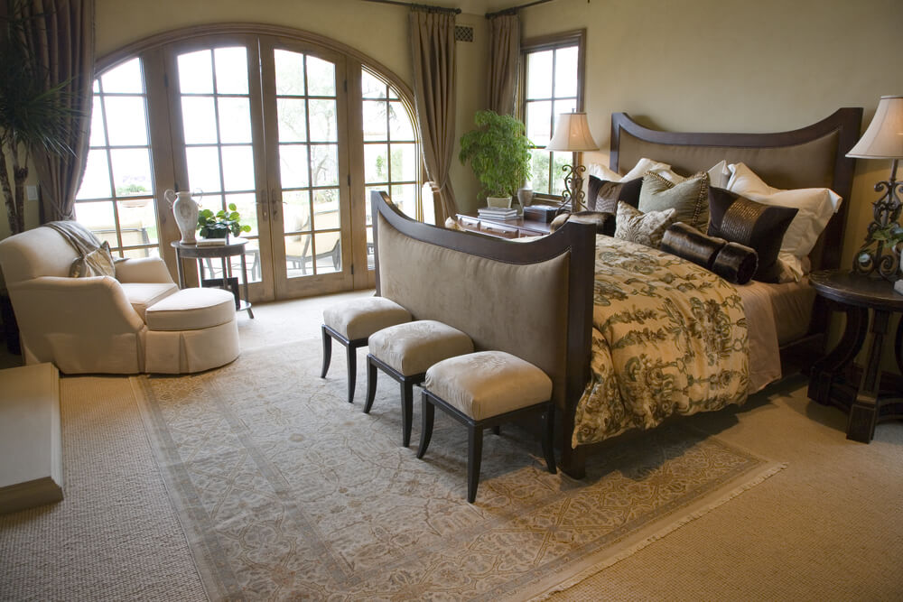 Luxury master bedroom comforters and curtains. Beautiful relaxing room with plenty of natural light, beige carpet, walls and furniture. In contrast with dark wood frame glass windows and dark wood bed frame and pillows.