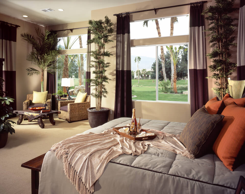Master bedroom bedding sets queen taupe bedding safari themes design and ideas. Big and spacious bedroom with pot tall plants and ornaments. Champagne on the bed and two color drapes.