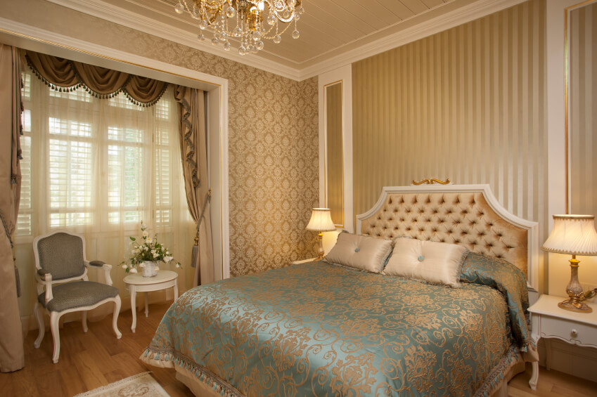 Master bedroom decor pictures blues browns golds accessories and insertions. Beautiful golden and crystal chandelier, golden ceiling and golden wallpaper on wall, blue and gold bed cover sheet with golden pillows.