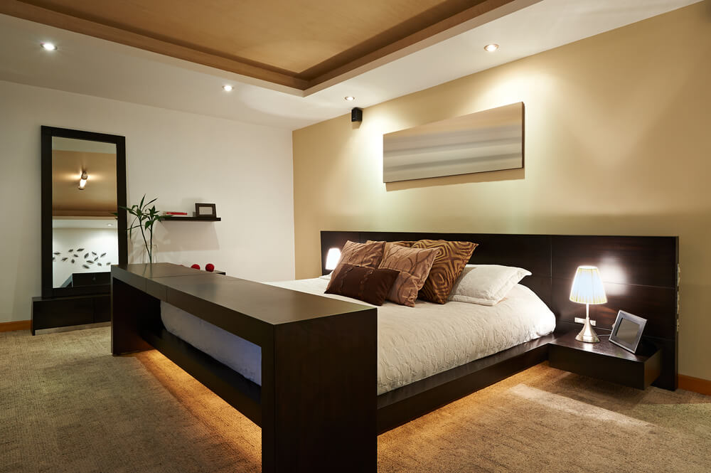 Modern master bedroom decorating ideas bedroom designs, simple design with dark brown bed frame and mirror and spot lights under the bed and on the ceiling. Light brown ceiling and white and brown walls.