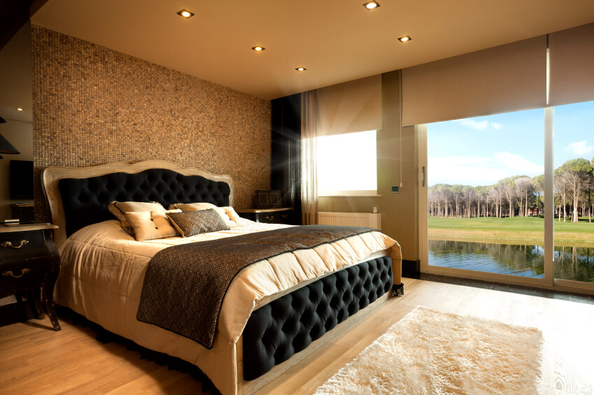 Modern master bedroom decorating ideas brown walls with black and beige classical kink size bed, tall retractile windows that lets sunlight come through, beautiful view over the lake with trees. Modern black furniture and light spots form ceiling.