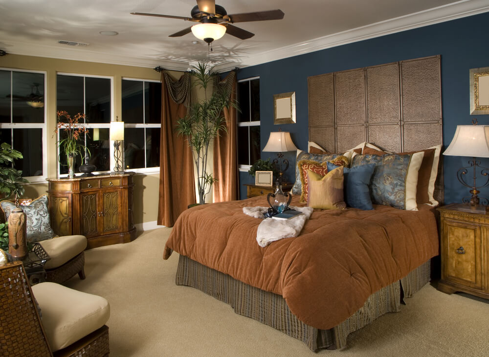 Master bedroom decorating ideas for small spaces with ceiling fan with lights and five blades. Brown bed cover and wood furniture in contrast with dark blue wall color. Many plants added and also two brown chairs for relaxing.