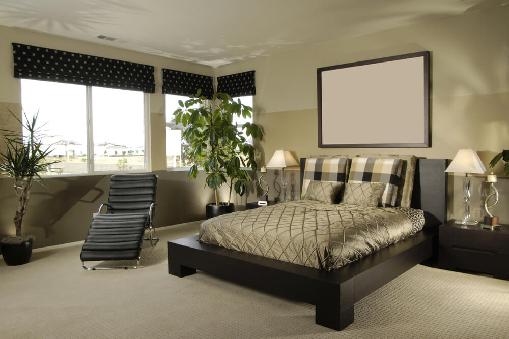 Master bedroom decorating ideas on a budget pictures of flowers that are in every corner of the room. Black wood frame bed and long chair also black drapes with decorations. Simple monochromatic picture over the luxurious bed and simple modern furniture.