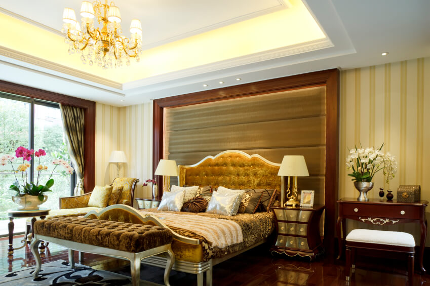 Master bedroom decorating ideas photo gallery with golden chandelier and gold ornaments and insertions. Dark and shiny brown pieces of classical furniture and a beautiful queen size golden bed. Gold and white lines as wallpapers.