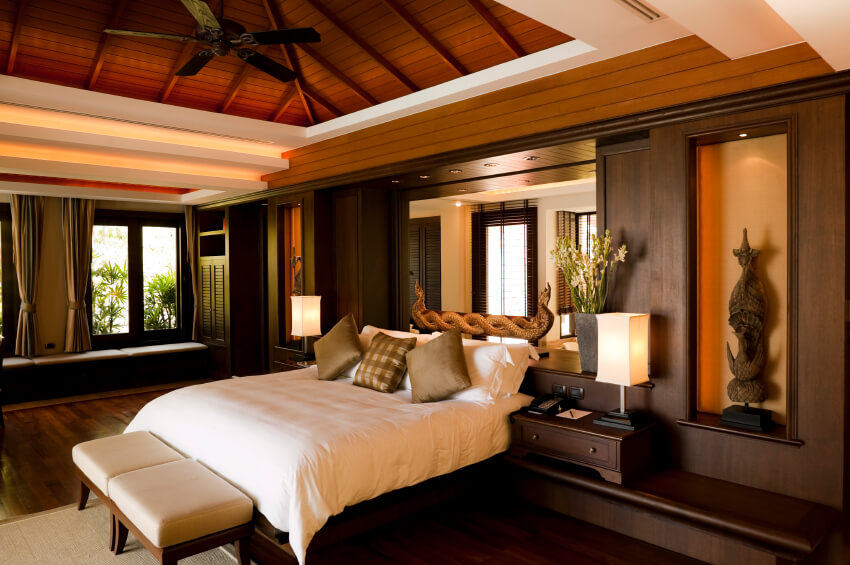 Master bedroom decorating ideas with dark furniture modern design ideas. Attic wooden ceiling with large five bladed fan and large wooden wall with statues and a big mirror over the queen size dark wood bed. Modern dark wooded furniture and a stylish white bed makes a great combination.