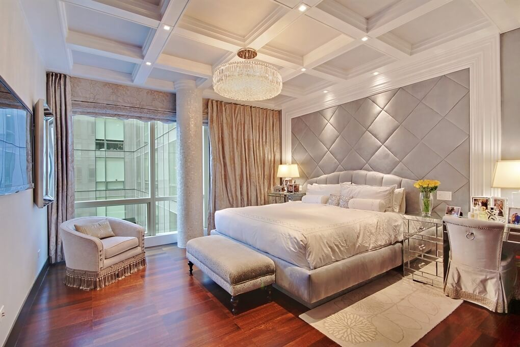Modern master bedroom decorating ideas with gray walls and brown and shiny hardwood flooring ideas and design. The ceiling has a beautiful crystal chandelier and light spots. The night stands covered with mirrors and there are two grey chairs, grey carpet and bed sheets.