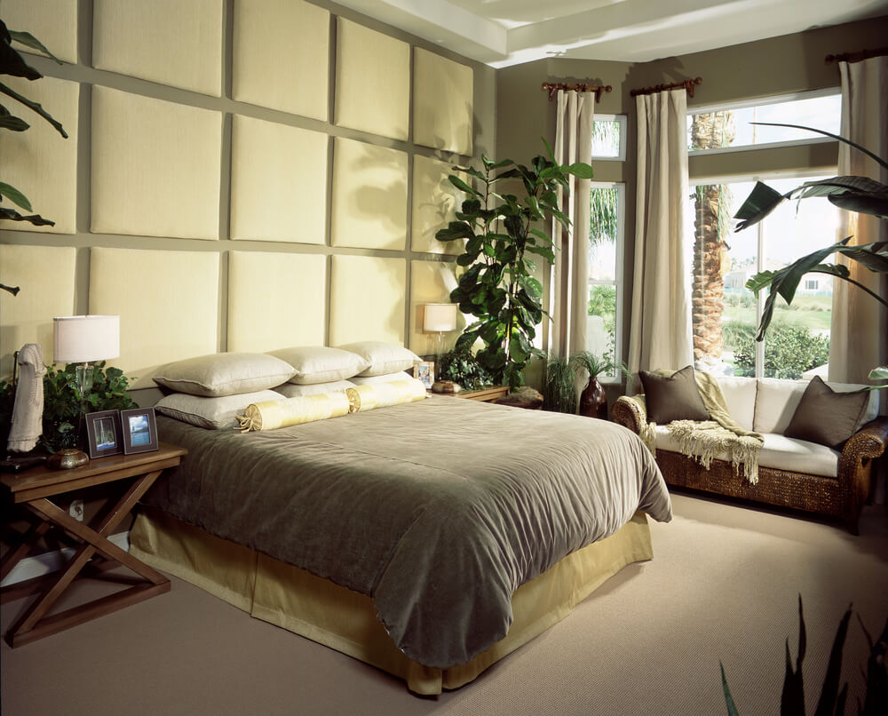 Master bedroom design ideas elegant style living with pale yellow square shaped wall design, plants on every corner of the bedroom and a splendid wooden loveseat near the bed.