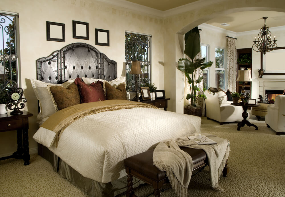 Master bedroom design ideas fireplaces wood with dark metallic chandelier and two white chairs with a dark wood coffee table. Tall white floral drapes. A big wall arcade that leads to a bedroom living room idea design and ideas.