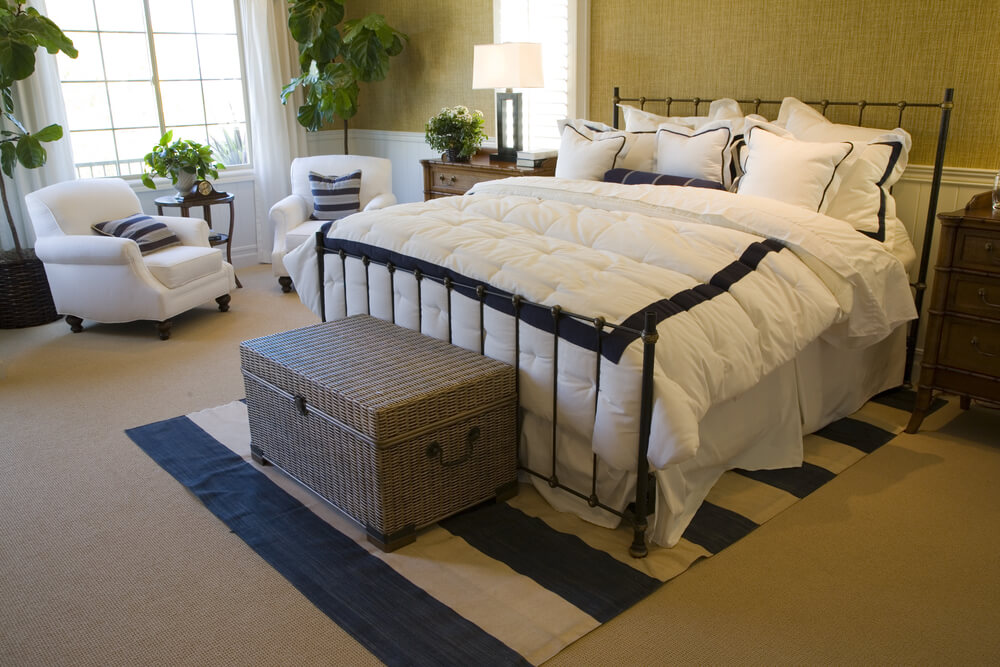 Master bedroom designs with sitting areas ideas - White bedding with two white reading chairs with blue & white pillows gives the room a lightness appearance. While not a big room, the beige scheme gives a cozy and comfortable appealing to the room.
