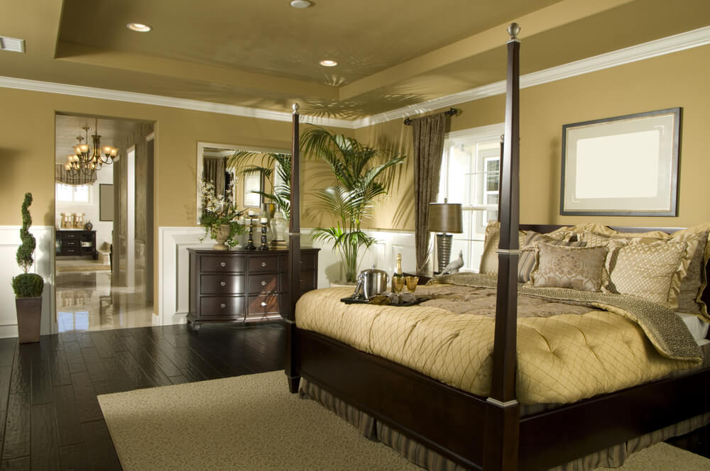 Master bedroom ideas with wallpaper accent wall bathroom with a large four-poster bed and a great beige and yellow themed color in contrast with a dark brown wood furniture and floor theme.