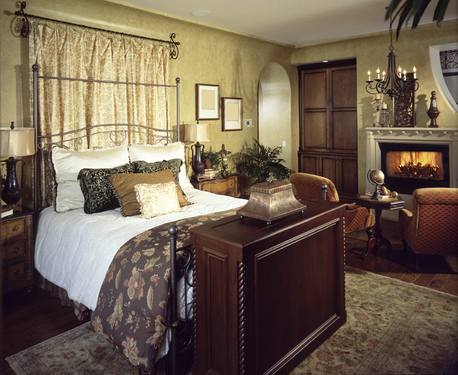 Master bedroom ideas with wallpaper accent wall images with a golden pattern, two orange seats in front of the fireplace and a wood small table. It has a massive stand at the foot of the queen sized metallic frame bed that hides the TV.