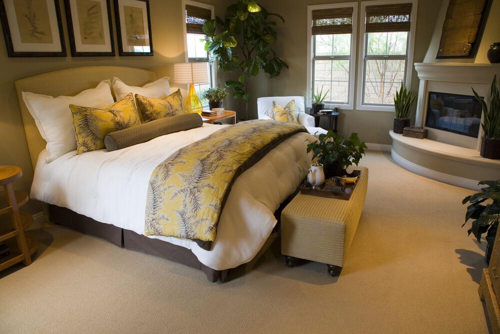 master bedroom makeovers some remodeling ideas with a fireplace in front of the bed and a small beige bench at the foot of the bed. Plenty of plants in the room and also at the coffee table. Yellow bed cover and pillows added in contrast with the green plants.