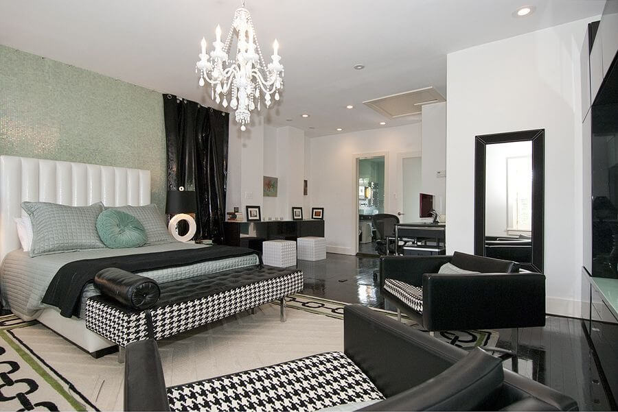 Black and white decor of the luxurious and modern master bedroom paint ideas bedroom decorating. White ceiling with white chandelier, black and white large chairs that faces a black bench at the foot of the bed. White carpet on top of the black shiny hardwood floor makes a great contrast.