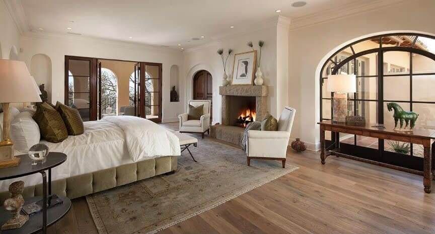 Classic master bedroom paint ideas high vaulted ceiling with a clay fireplace in front of the bed and who white chairs facing the small white bench on the foot of the bed. A balcony on the right side that is blocked by a traditional wood table. And on the left side a patio with wall columns.