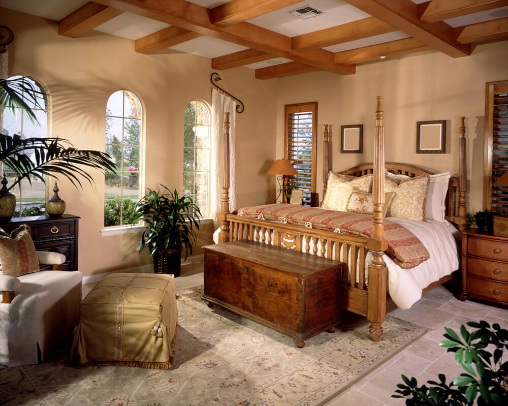 Master bedroom paint ideas with accent wall bedroom paint beige and with grey stone tile floor. A beautiful four-poster bed adds a traditional look to the room. At the foot of the bed is a small wooden bench with can be used for storage. Outside nature view trough the large arched white windows, witch allows plenty of natural light to come in.